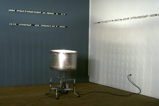 """LIMITED DOMAIN MEANING MACHINE (30"""" x 30"""" x 40"""") - When the viewer approaches the sculpture a light turns on and the washing machine tub with ping-pong balls inside rocks back and forth. Printed on each ball is a techno-speak word. Viewers may select ping-pong balls to place on a velcro strip on the wall to create meanings which are limited to techno-speak phrases."""
