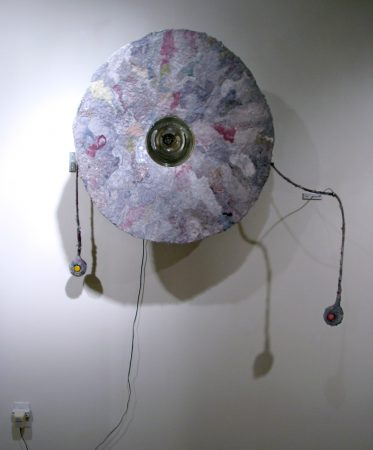 """MESSAGE SLOUGH (40"""" x 13"""" x 40"""") - Your messages can be recorded into the sculpture by speaking while pressing the red button and played back by pressing the yellow button, but our voice messages are like our lint, sloughing off, on answering machines around the world. Lint, buttons and sound sampler."""
